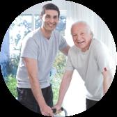 male caregiver assisting senior man with walker