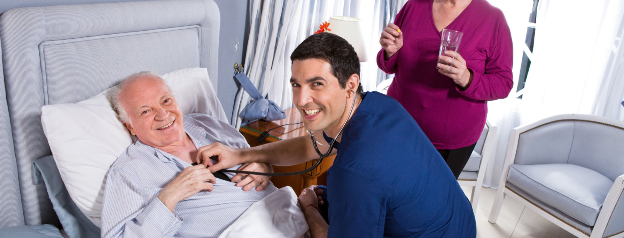caregiver checking the measure of heartbeat of senior man on the bed