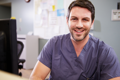 male nurse smiling at the nurse station