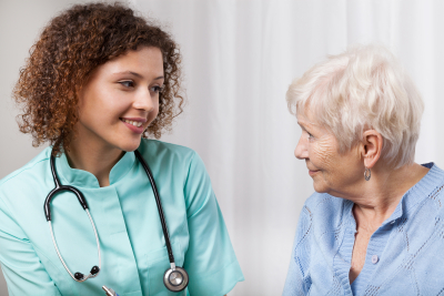 nurse having a conversation to senior woman